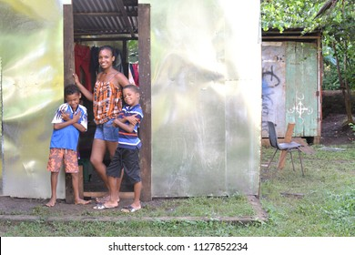 CORN ISLAND, NICARAGUA-NOVEMBER 16: A woman and two native Creole boys stand proudly in front of newly built zinc sheet metal house in Big Corn Island, Nicaragua, Central America on November 16, 2017.