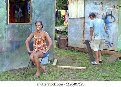 CORN ISLAND, NICARAGUA-NOVEMBER 16: A woman sits proudly in front of newly built zinc sheet metal house as man builds in Big Corn Island, Nicaragua, Central America on November 16, 2017.