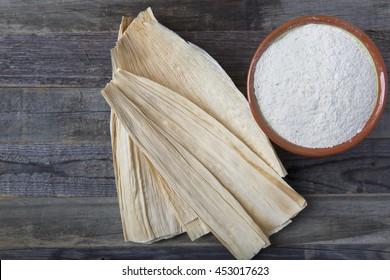 Corn masa flour and corn husks for preparing tamales.