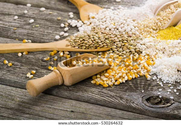 corn, millet, lentil, bean and other uncooked grain foods on old wood table background