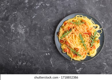 Corn noodles with tomato sauce and arugula on a black concrete background. Top view, flat lay, copy space.