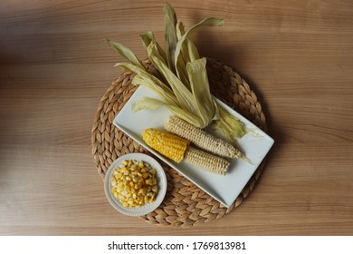 Corn on the cob with finished ears, husk, whiskers, and kernels. Eating corn kernel by kernel. Unconventional way of eating corn.