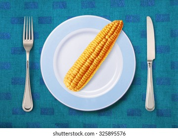 corn on white plate with knife and fork