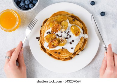 Corn pancakes with caramelized bananas, natural yogurt and chocolate chips on white plate. Girl eating pancakes for breakfast. First person view, top view