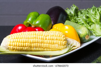 Corn, paprika, cucumber and lettuce on white plate.
