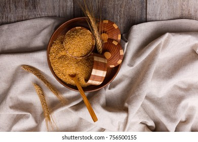 Corn porridge in a wooden plate with wheat spikes on a cloth on a close-up table