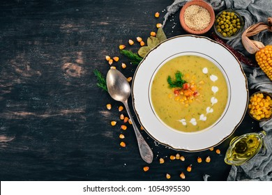 Corn soup with fresh vegetables in a bowl. Healthy food. On a black wooden background. Top view. Copy space for your text.