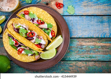 corn tacos with pork and vegetables on a wooden table. top view