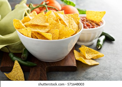 Corn tortilla chips in big bowl with tomato salsa