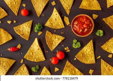 corn tortilla chips nachos and chunky tomato salsa in a wooden bowl cherry tomatoes