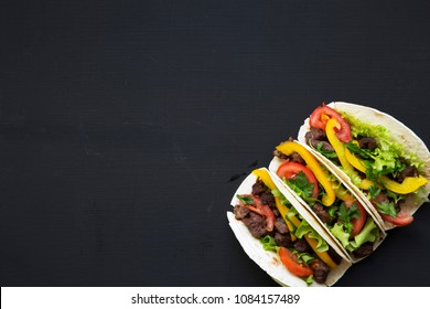 Corn tortillas with beef and vegetables on a black background, top view. Mexican kitchen. Copy space. Flat lay.