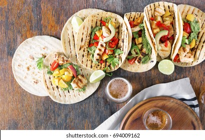 Corn tortillas with grilled chicken fillet, guacamole sauce and beer on wooden table, top view
