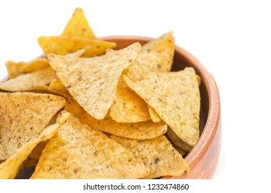 Corn tortillas or nachos, fried over an open fire, lie in a wooden bowl. Copy space