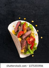 Cornbread with beef, vegetables and pineapples and corn grains on a wooden kitchen Board. Food preparation. Taco al pastor on a black wooden Board. Top view with copy space