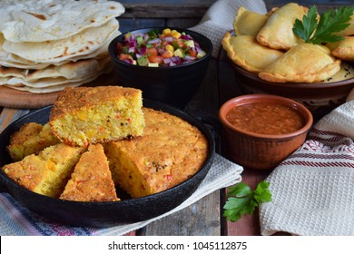 Cornbread and other mexican food - tacos, salsa with tomato, red onion, lime, cilantro, corn and hot pepper sauce, empanadas. Copy space.