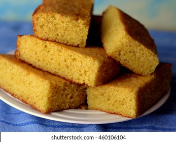 Cornbread squares stacked on a white plate: Closeup on a blue background.