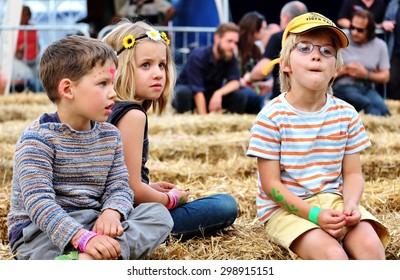 Cornbury Festival - July 11 2015: Children  sitting on hay bales enjoying  Cornbury Festival,  Great Tew Park, Chipping Norton, Oxfordshire, July 11, 2015 in Oxfordshire, UK