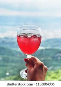 Cornelian cherry fresh juice, Albanian traditional refreshing drink. Blurred background with view to Tirana.