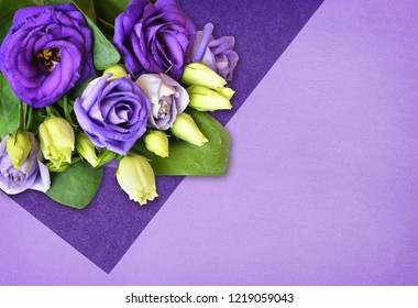 Corner arrangement with lisianthus flowers on modern flat lay background with papers of different shades of purple