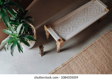 A corner bird eye view of a bench made of wood and white fabric on the right side of it there is a medium size plant pot with a green leafy plant, in front there is a small muniment and a brown carpet