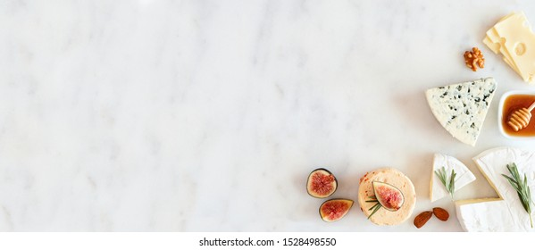 Corner border of a selection of cheeses, figs, nuts and honey. Above view banner on a white marble background with copy space.