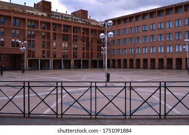 corner with  brick buillding y metal balaustrecorner with brick buildings and metal railing in the foreground in the Plaza de la Remonta in Madrid. Spain