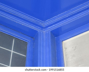 the corner of a bright cobalt blue painted frontdoor and ceiling