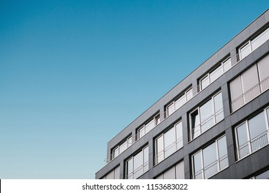 The corner of the building with many windows in a minimalistic style against the blue sky.