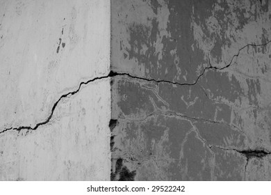Corner of a concrete wall with cracks and chips