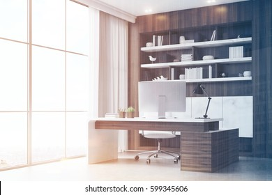 Corner of a dark wooden workplace with a table, a desktop standing on it and a bookcase behind it. Poster on the wall. 3d rendering. Mock up. Toned iamge