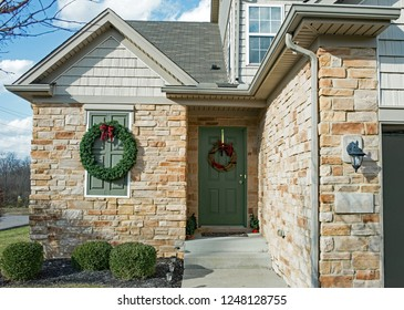 Corner entrance of tan stone house decorate with Christmas evergreen wreath and grapevine wreath on door.