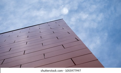 The corner exterior wall of of skyscraper of metal aluminium composite panels. The wall is orange in color and stands in front of blue sky with lots of clouds. The building stretches up on a diagonal