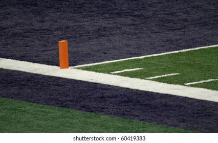 Corner of a football field blue end zone with orange pylon