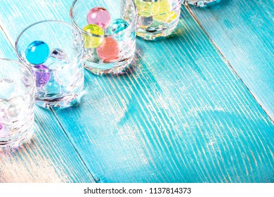 in the corner of the frame shot glasses under vodka in which colored balloons are filled, blue color of boards on which there are glasses