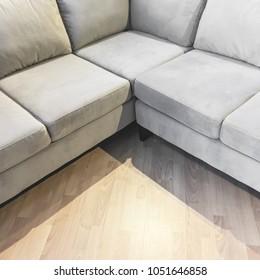 Corner gray velvet sofa on a laminated floor.