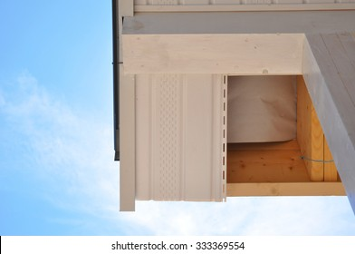 Corner of house with eaves against summer background. Install soffits. Roofing Repair Soffit Board and Fascia Board. Fascias and Soffits are the Boards that Cover the Ends of the Roof Rafters.