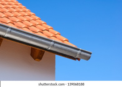 Corner of the house with gutters and ceramic tile roof on a background of blue sky.