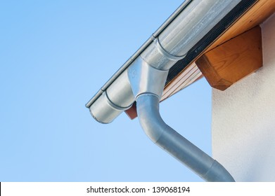 Corner of the house with gutters on a background of blue sky.
