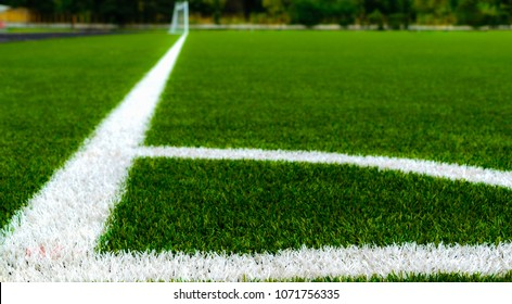 Corner kick area on an empty football field, under a strong summer sun