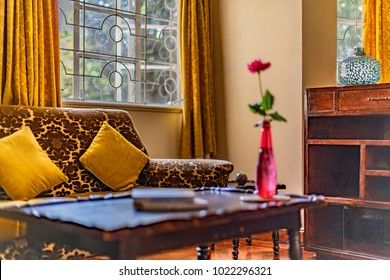 Corner of lounge room decorated with vintage furniture of mid 20th century.Brown and gold colors dominate.Sofa upholstery is velvet. Sideboard is timber.Fashion of 1950s, 1960s, 1970s.Selective focus