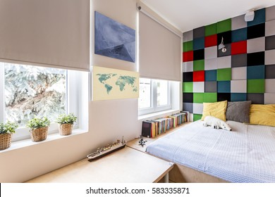 Corner of a modern bedroom with large fitted bed and patchwork wall