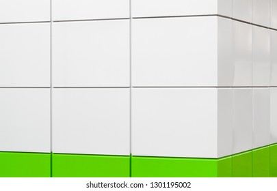 Corner of modern building facade made of white and green metal plates