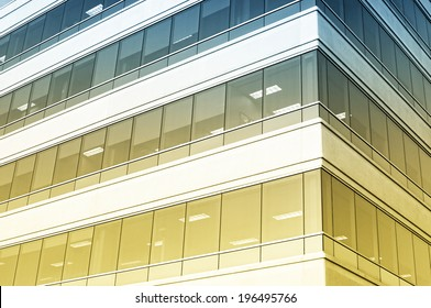 The corner of an office building with rows of windows ranging from yellow to dark blue.