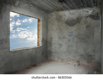 corner of old concrete room with blue sky window