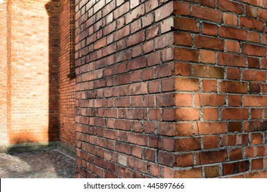 Corner of old house with cracked red brick building with a view on the street