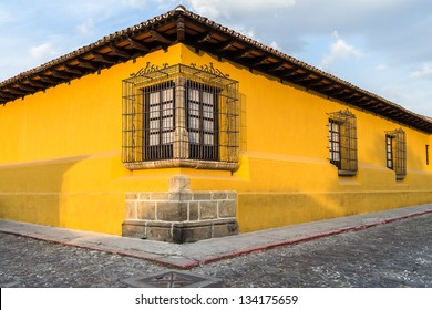 Corner perspective of a bright yellow colonial house with barred windows in Antigua, Guatemala.