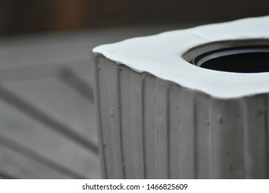 Corner of an plant pot on a teak wooden table in the autumn.