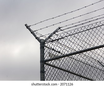 Corner post of a chain-link fence topped with barbed wire.