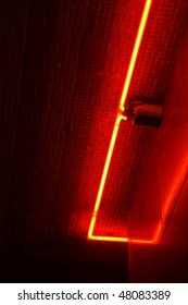 The corner of a red neon border, reflecting off of the tile above and beside.