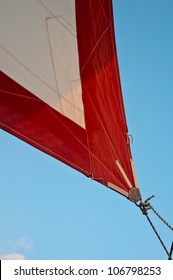 Corner of red and white jib sail with jibsheet showing